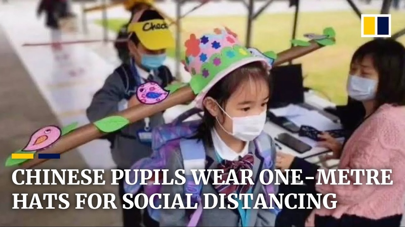 Chinese pupils wear one metre hats to practise social distancing from others