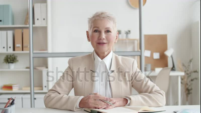 Stock footage pov waist up shot of smiling mature caucasian lady with short grey hair in business suit and white